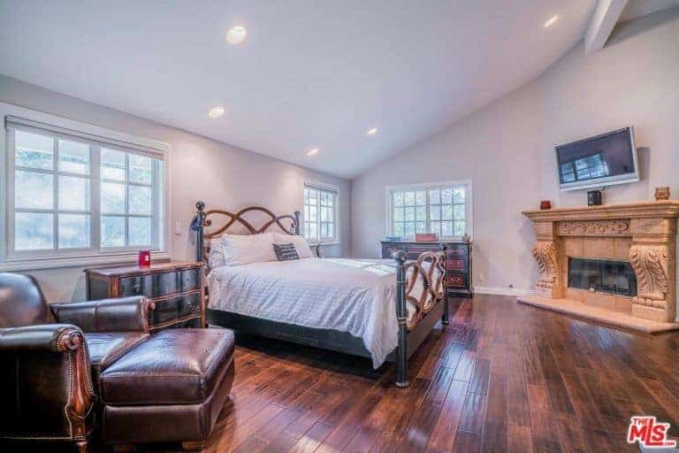 Large primary bedroom featuring hardwood flooring and a shed ceiling. The room boasts a large classy bed along with a beautifully decorated fireplace with a widescreen TV on top of it.