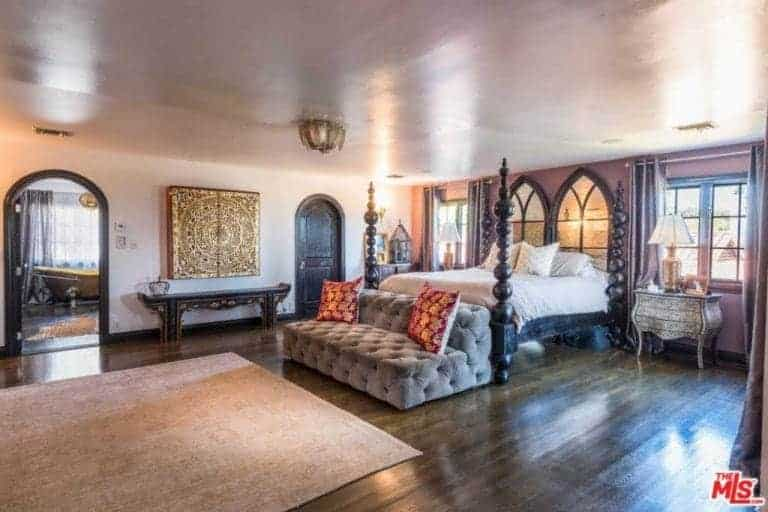 Huge primary bedroom boasting an elegant bed set along with a luxurious gray couch and classy table lamps on both sides of the bed. The room also has a large primary bathroom featuring a gold-finished freestanding tub.