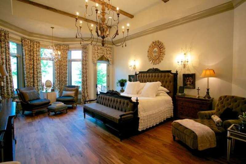 Large primary bedroom featuring a luxurious bed set lighted by wall lights and a glamorous chandelier. The room has hardwood flooring, a tray ceiling with beams and elegant window curtains.