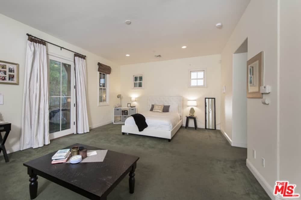 Spacious primary bedroom with white walls and ceiling, along with dark gray carpeted flooring. The room has a nice bed lighted by table lamps.