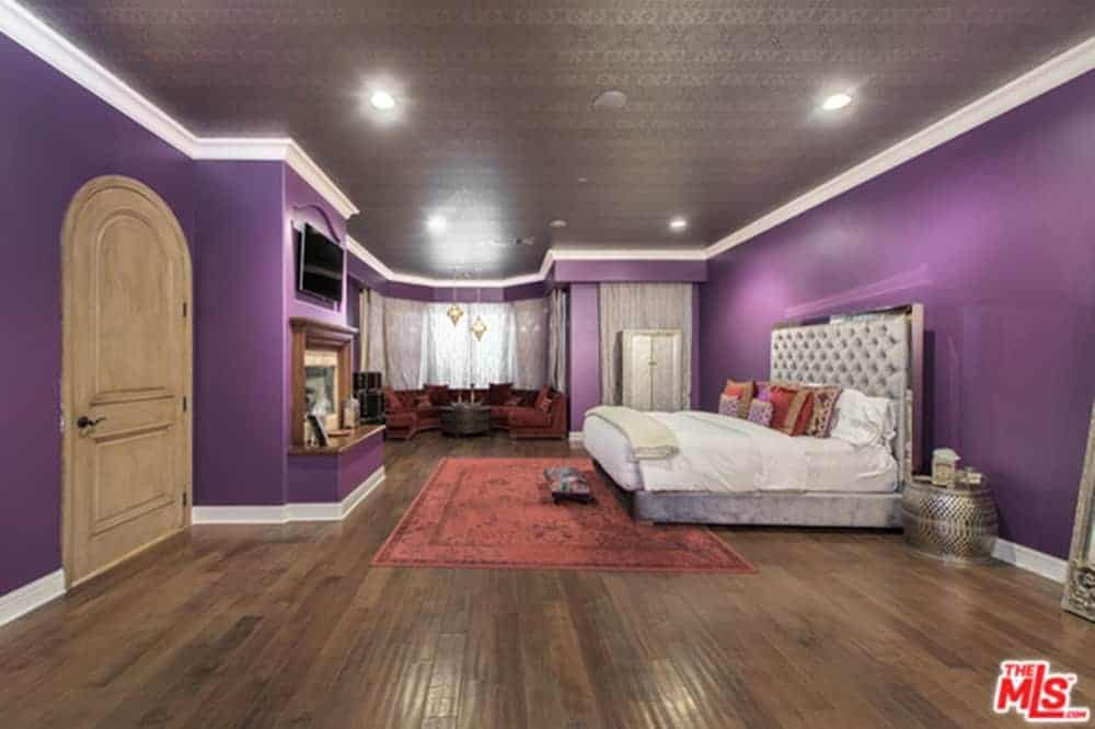 Large primary bedroom boasting a luxuriously large bed surrounded by purple walls and a brown decorated ceiling, along with hardwood flooring.
