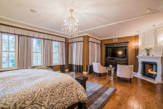 Large primary bedroom with brown walls and hardwood floors. It offers a large cozy bed and a fireplace, along with a living space on the side featuring a TV.