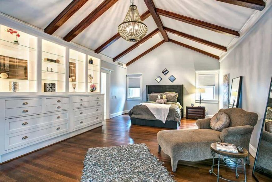 Primary bedroom with white walls and hardwood flooring, along with a vaulted ceiling with exposed beams. The room offers large cabinetry and shelving with its own lighting.