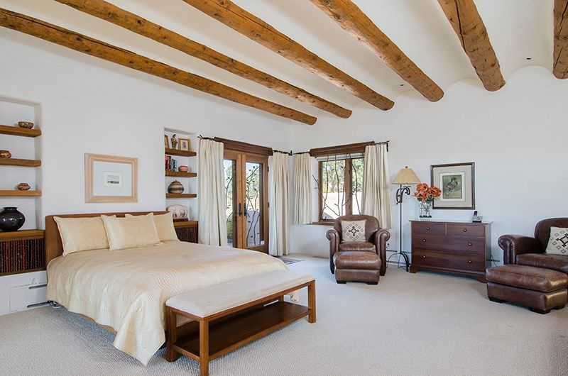 Large primary bedroom with a nice bed along with built-in shelves on both sides. The room is surrounded by white walls and a white ceiling with exposed beams along with carpeted flooring.