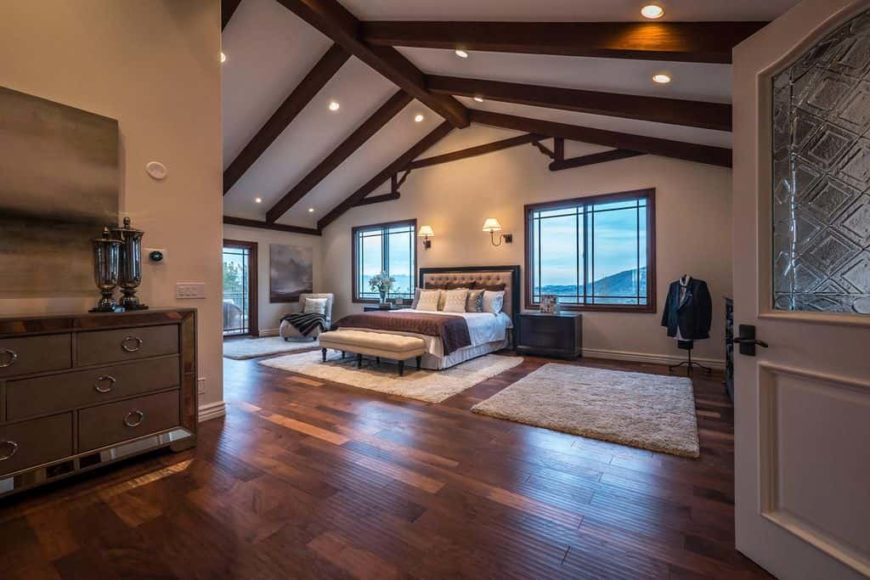 Large primary bedroom with a vaulted ceiling with exposed beams together with hardwood flooring. The room offers a classy bed lighted by wall lights.