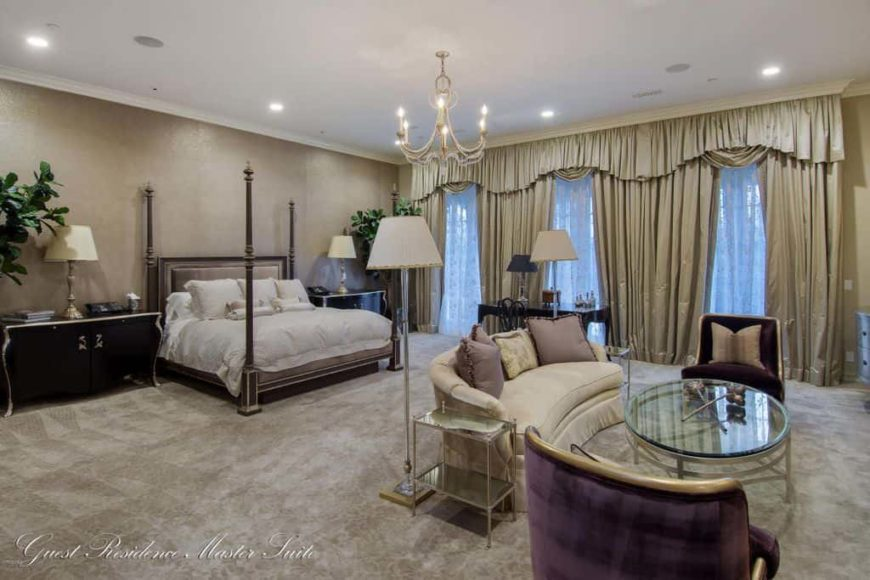 Large primary bedroom featuring an elegant bed set along with a personal living space with a set of classy furniture. The room features a gorgeous chandelier, lovely window curtains and gray carpet flooring.