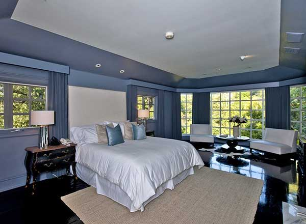 Large primary bedroom featuring blueish gray walls and dark hardwood floors. The room offers a comfy bed lighted by classy table lamps. The room also offers a sitting space on the side.
