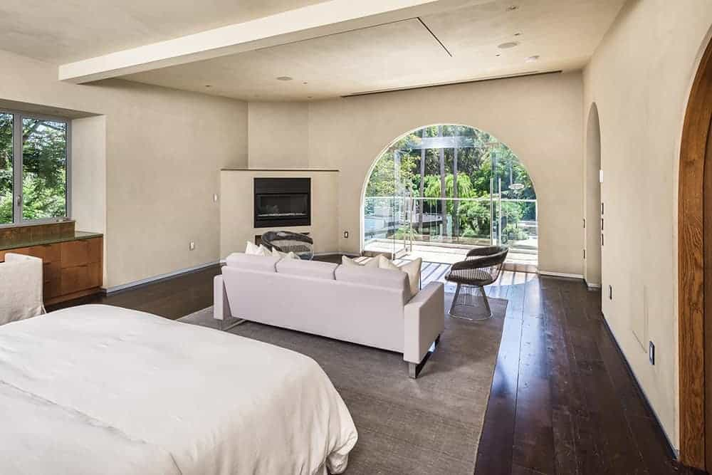 Mediterranean primary bedroom featuring hardwood flooring. The room offers its own living space featuring a white couch and a fireplace in the corner.
