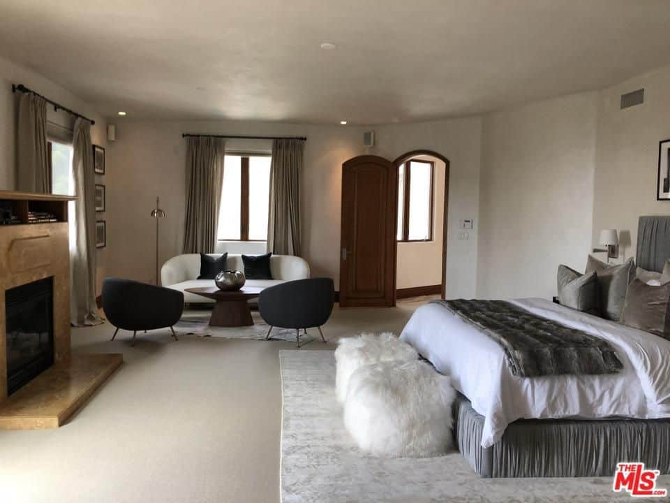 Large primary bedroom featuring a large cozy bed and a small living space on the side. The room also offers a fireplace.