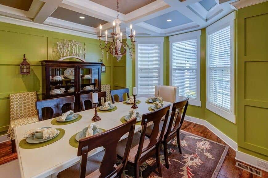 This dining room has avocado green walls with an elegant wooden finish that complements the white coffered ceiling that hangs a chandelier over the white wooden dining table that is contrasted by the dark wooden chairs and the dining room cabinet.