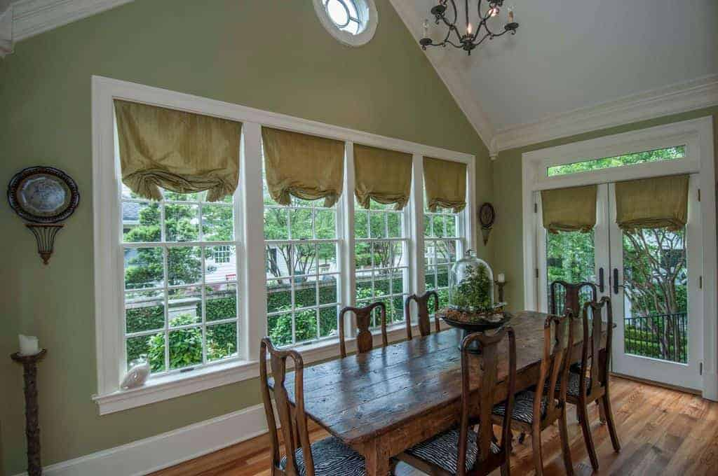 This simple country-style dining room has a white cathedral ceiling that bears a wrought iron chandelier over the wooden dining table and its wooden chairs that match with the hardwood flooring and complemented by the green walls and its glass windows.