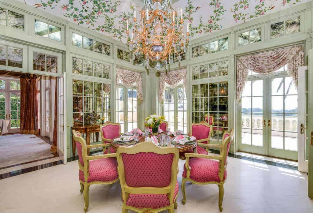 The elegant dining chairs surrounding the round wooden table has golden frames and pink patterned cushions that stand out against the light gray carpeted flooring. This simple flooring is contrasted by the floral ceiling with a majestic chandelier.