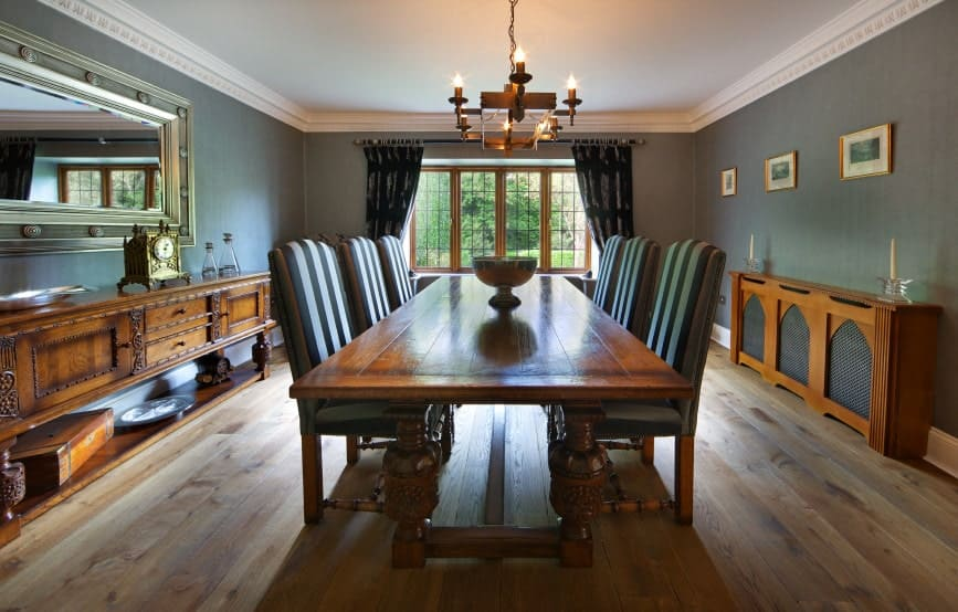 This country-style dining room has a certain warmth to its hardwood flooring that complements the wooden dining table and the two wooden cabinets that stand out against the gray walls that match with the cushions of the dining chairs.