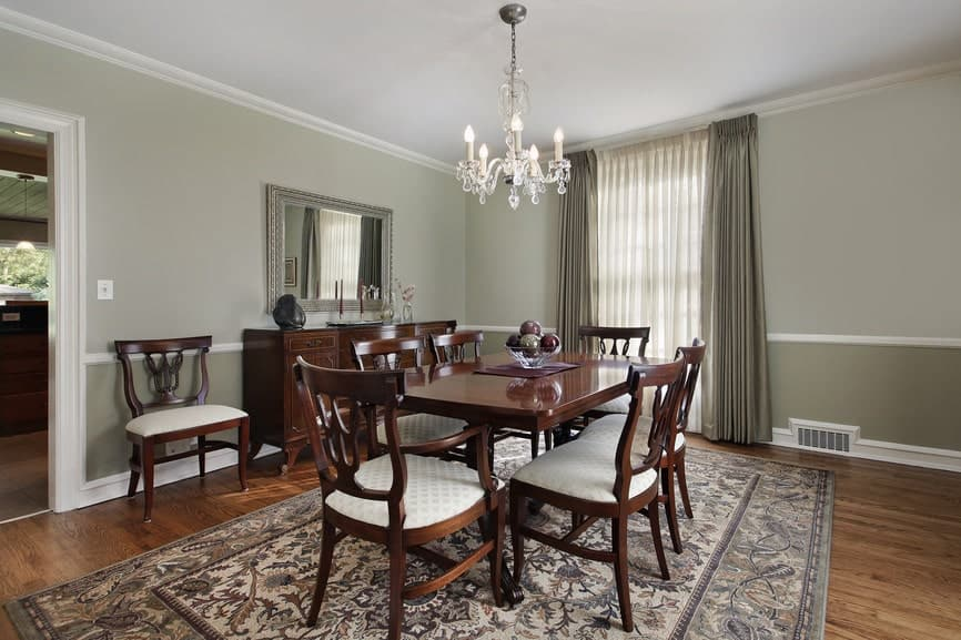 The light green walls makes the dark wooden dining set stand out as well as its colorful patterned area rug that is illuminated by the curtained window by the head of the table. The window is augmented by the crystal chandelier.