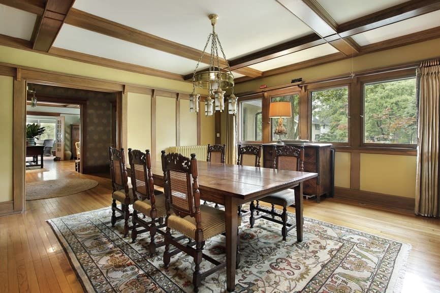 The charming patterned area rug complements the rectangular wooden table and its dining chairs that has woven wicker backs and beige seats. This is paired with a golden chandelier hanging from the white coffered ceiling.