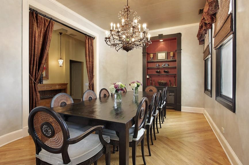 The long rectangular wooden dining table has a dark brown hue that matches with the cabinet that is embedded into the light gray wall. It has a dark wooden frame that complements the light hardwood flooring and ceiling.