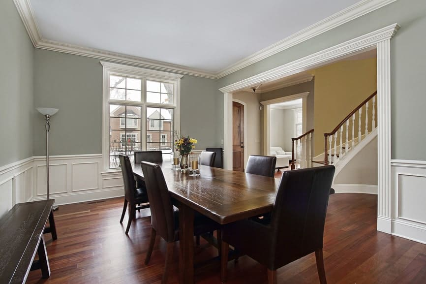 The light gray walls of this dining room is complemented by the white wainscoting that contrasts the dark hardwood flooring and the dark wooden bench pressed against the wall beside the wooden dining set that has black leather cushions on its chairs.
