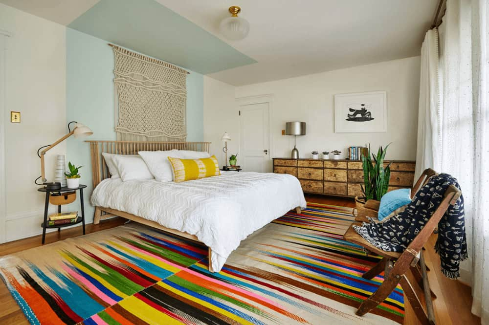 An eye-catching multi-colored rug adds a striking accent in this primary bedroom showcasing a wooden bed and long distressed dresser topped with a chrome table lamp.