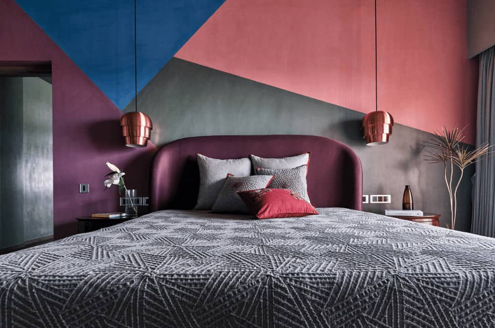 Multi-colored bedroom features a plum bed with gray textured bedding accompanied by wooden nightstands and stylish pendant lights.