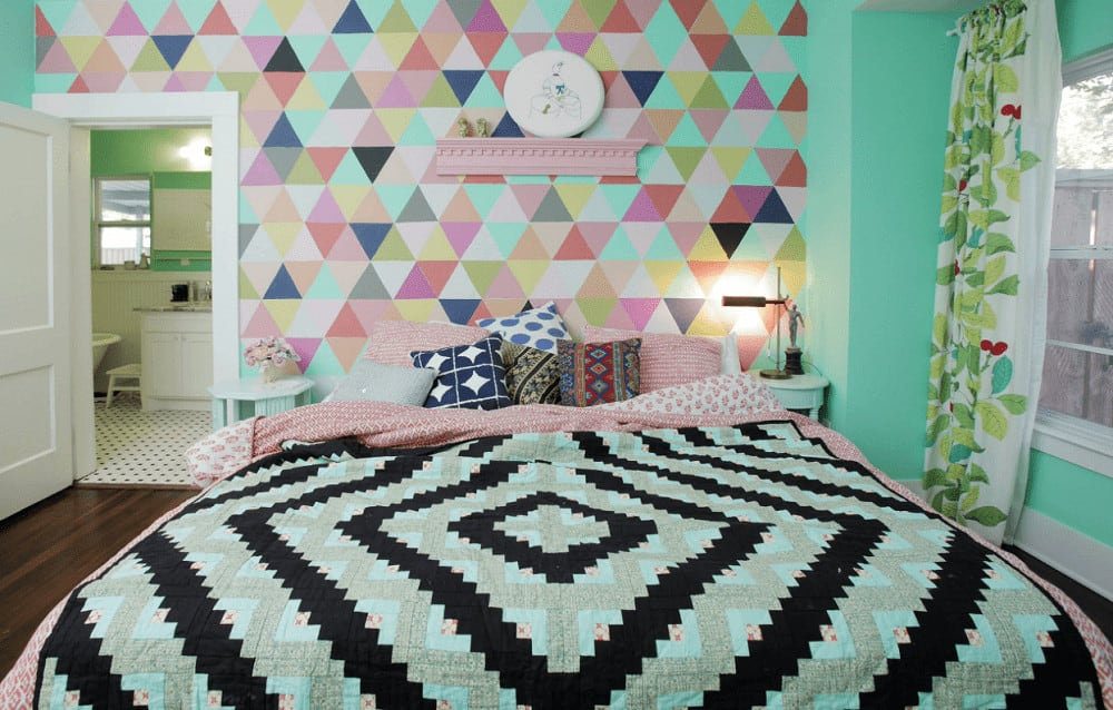 A multi-color patterned wall adds a striking accent in this charming bedroom with a comfy bed and pink floating shelf topped with mini sculptures and round wall art.