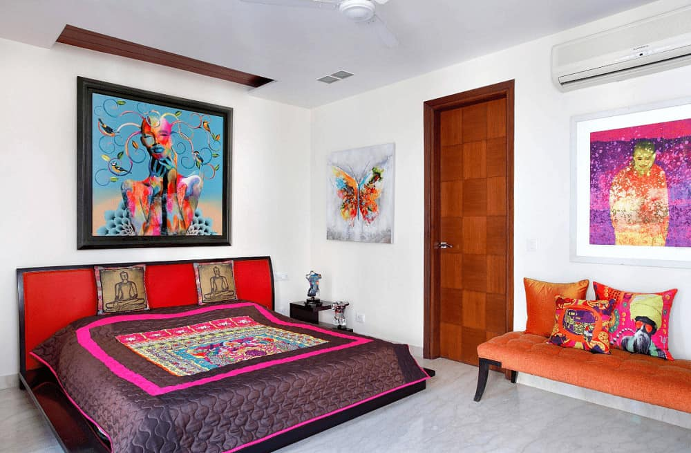 Eclectic bedroom offers an orange tufted bench and red platform bed paired with a dark wood nightstand. It is accented with gorgeous artworks mounted on the white walls.