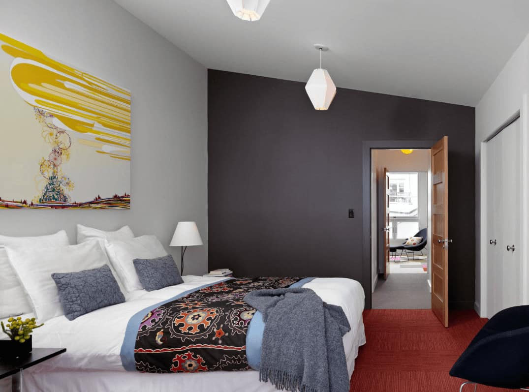 This primary bedroom is decorated with white geometric pendants and lovely painting that hung above the white skirted bed accented with a black patterned coverlet.