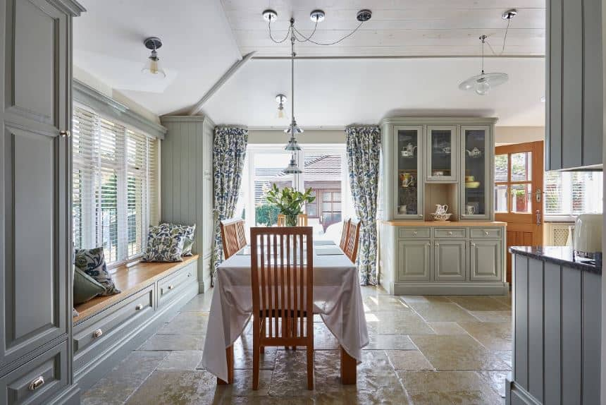 This dining area oozes with charm and homey quality. It has a rectangular wooden dining table covered in white cloth that makes the slat backed dining chairs stand out. These wooden elements go well with the beige textured flooring that is illuminated by the windows.