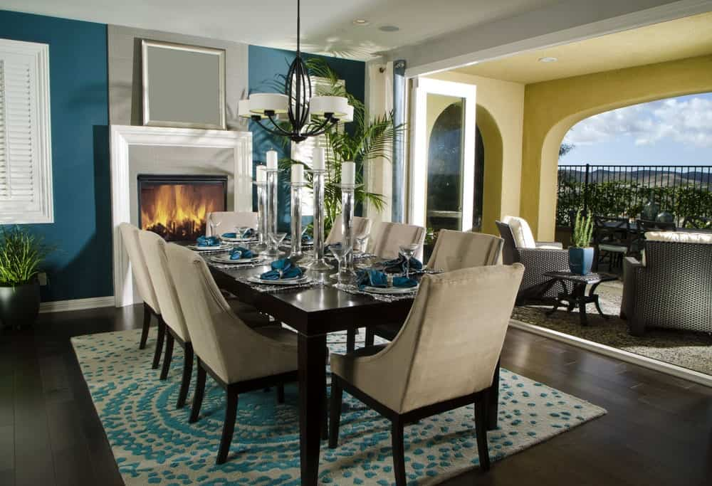This lovely Mediterranean-style dining room has a blue patterned area rug that matches with the blue walls that house a white fireplace and it also matches with the table napkins of the elegant dark wooden table paired with light gray cushioned chairs.