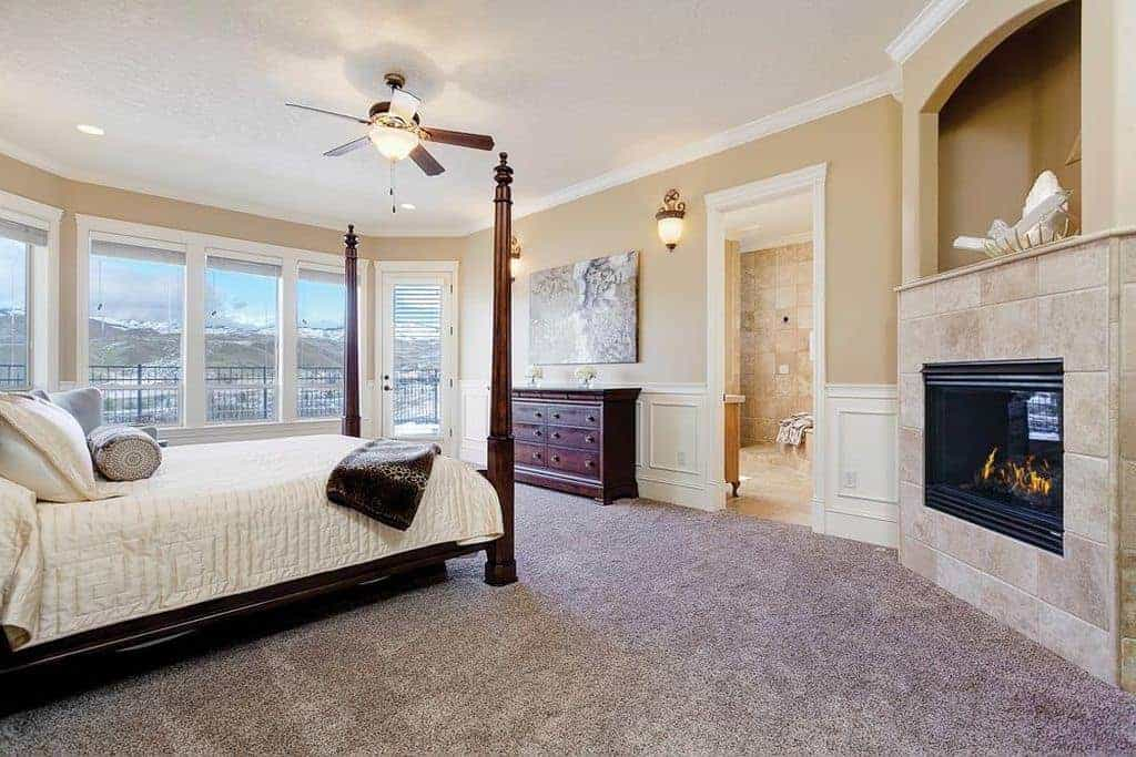 Sophisticated primary bedroom with carpet flooring and glass paneled windows inviting natural light in. It includes a modern fireplace and four poster bed that complements the wooden dresser.