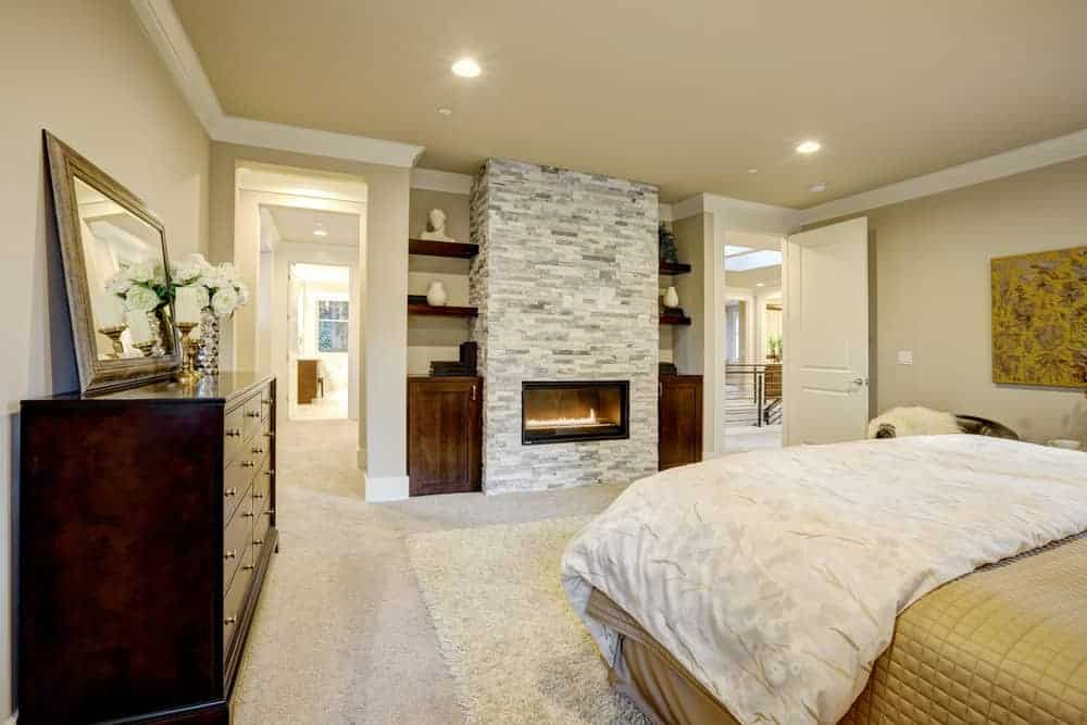 This primary bedroom showcases a comfy bed and glass enclosed fireplace fitted on the brick pillar. It includes built-in shelving and dark wood dresser topped with mirror and glass flower vase.