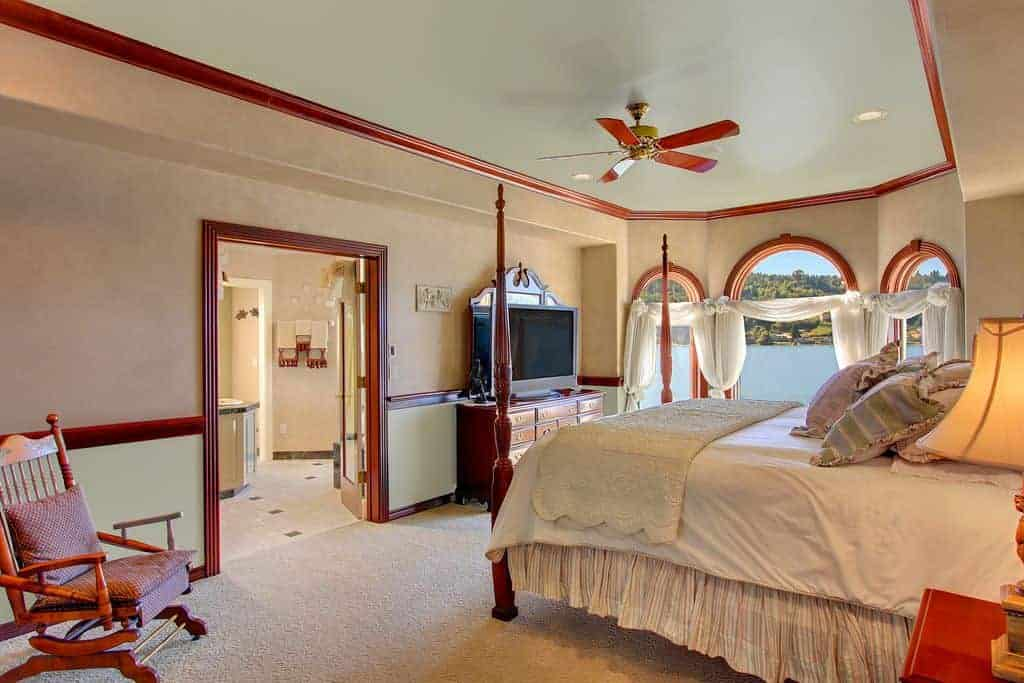 Beige primary bedroom lined with redwood moldings that complement the four poster bed, dresser and wooden armchair. It has a ceiling fan and arched windows dressed in white sheer curtains.
