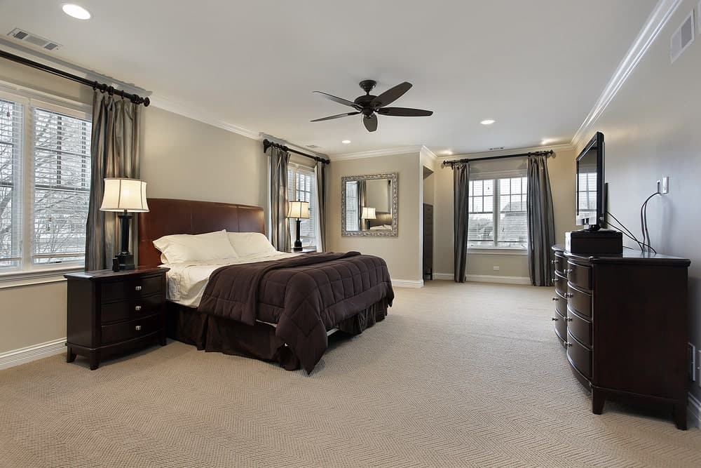 A dark wood dresser complements the nightstands topped with traditional table lamps. There's a leather bed in the middle wrapped in a brown comforter.