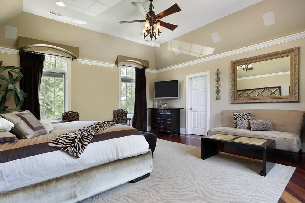 Elegant bedroom with a velvet bed and sofa accompanied by an ornate mirror and dark wood coffee table. It has glazed windows and hardwood flooring topped by a textured area rug.