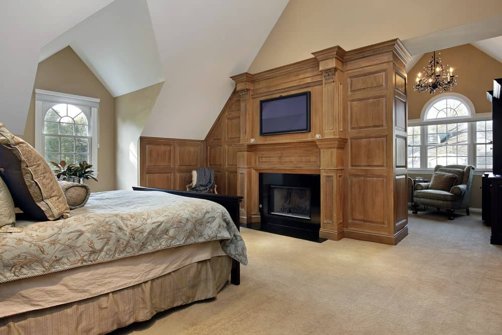 This primary bedroom boasts a skirted bed and a seating area behind the fireplace lighted by a gorgeous candle chandelier. It includes a flat screen TV fitted on the wood paneled wall.