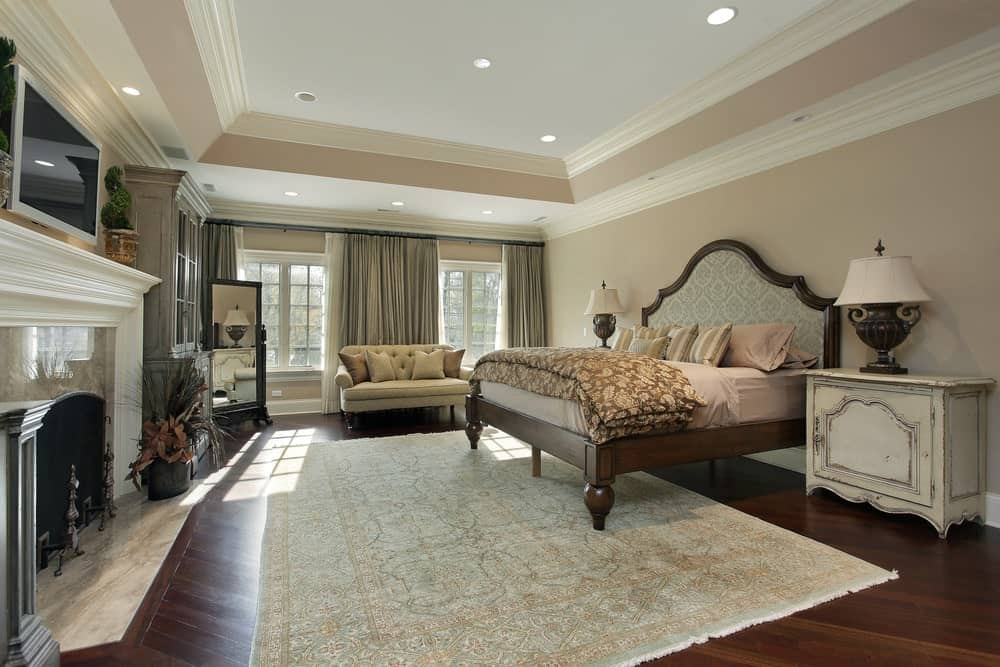 Natural light streams in through the white framed windows in this primary bedroom with a marble fireplace and wooden bed situated in between distressed nightstands.