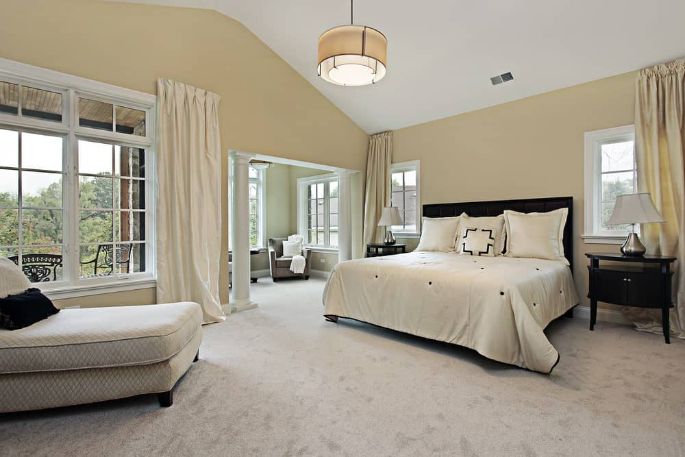 Spacious bedroom boasts a velvet armchair and patterned chaise lounge that faces the dark wood bed illuminated by chrome table lamps and drum pendant light.