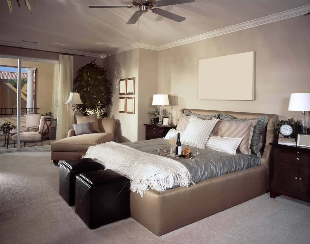 Beige primary bedroom with dark wood nightstands and upholstered bed accompanied by a matching chaise lounge and black ottomans.