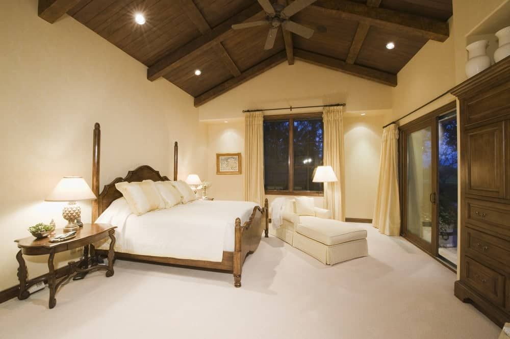A skirted chaise lounge sits near the wooden two poster bed in this beige bedroom with carpet flooring and vaulted ceiling clad in dark wood planks.