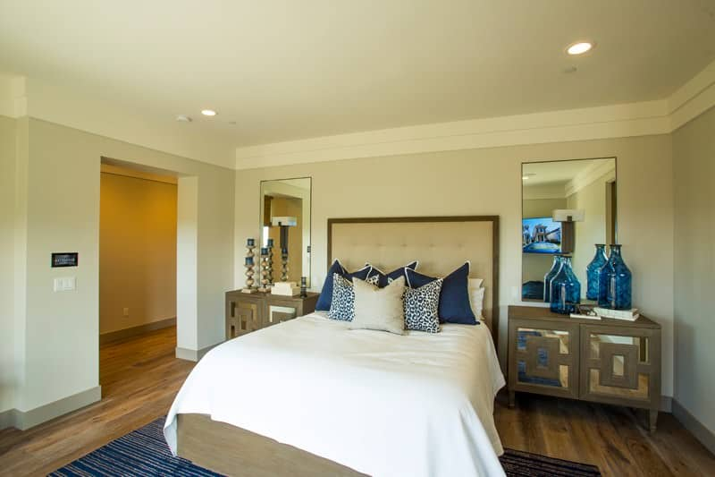 Simple bedroom with mirrors and a tufted bed that sits on a blue striped rug. It includes stylish nightstands topped with candle holders and translucent vases.