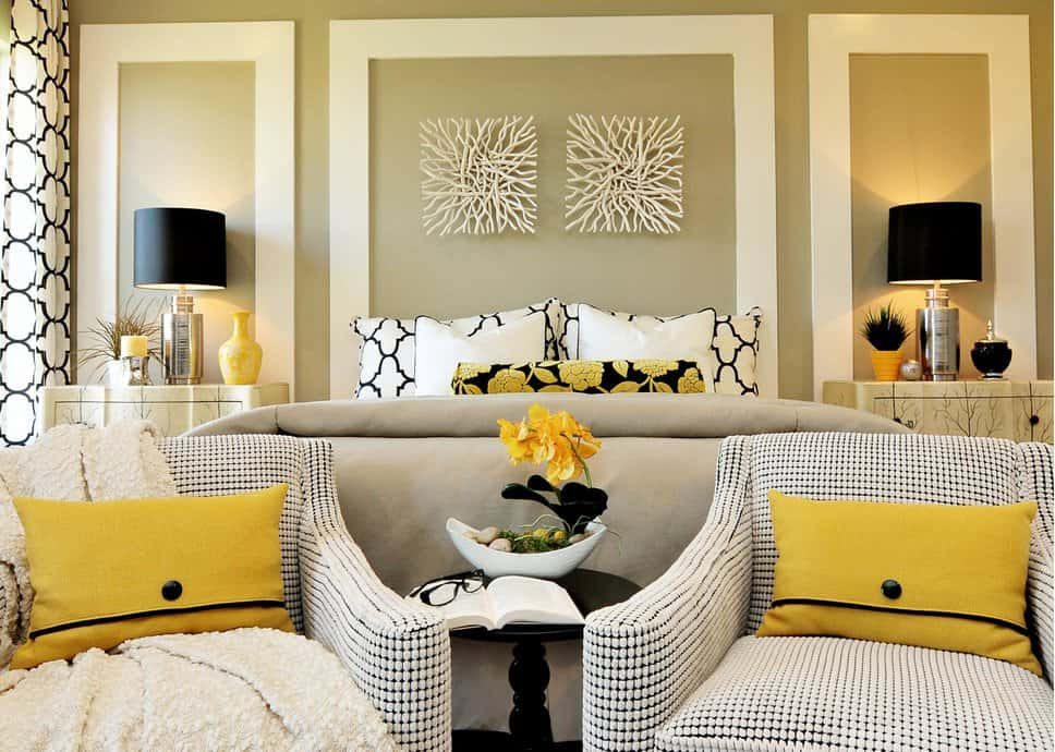 A pair of driftwood wall arts hang above the bed in this fabulous primary bedroom with black table lamps and patterned armchairs accented with yellow pillows.