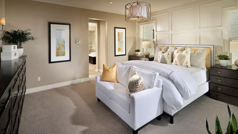 A stylish drum pendant light illuminates this beige primary bedroom boasting white bed and loveseat contrasted by darkwood nightstands and dresser.