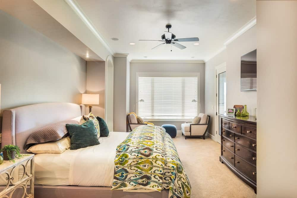 Fresh primary bedroom showcases a seating area and an upholstered bed facing the wooden dresser and frameless mirror. It has carpet flooring and regular ceiling mounted with fan and recessed lights.