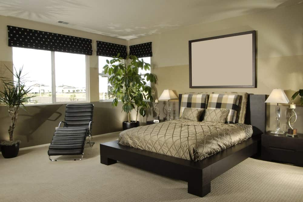 Fresh primary bedroom with three-tone walls and glazed windows covered in black dotted roman shades. It includes a black lounge chair and platform bed lighted by glass table lamps.