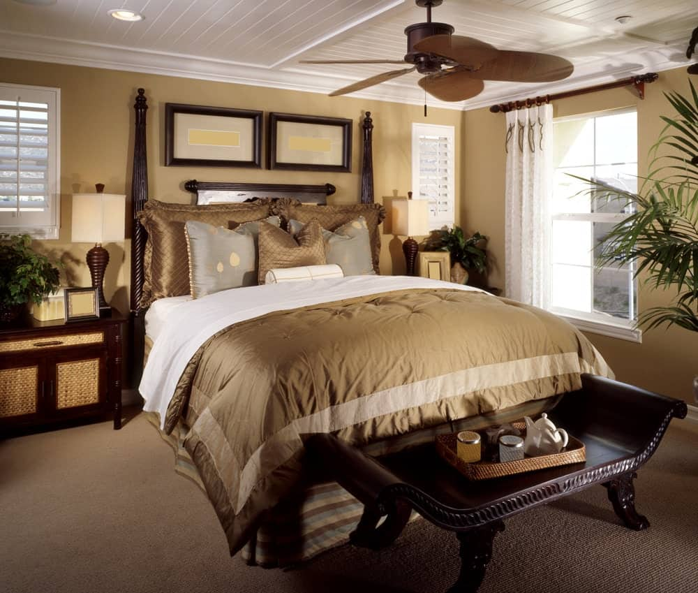 Tropical primary bedroom boasts a classy bed and bench over carpet flooring. It includes a ceiling fan and wooden nightstands topped with sleek table lamps.