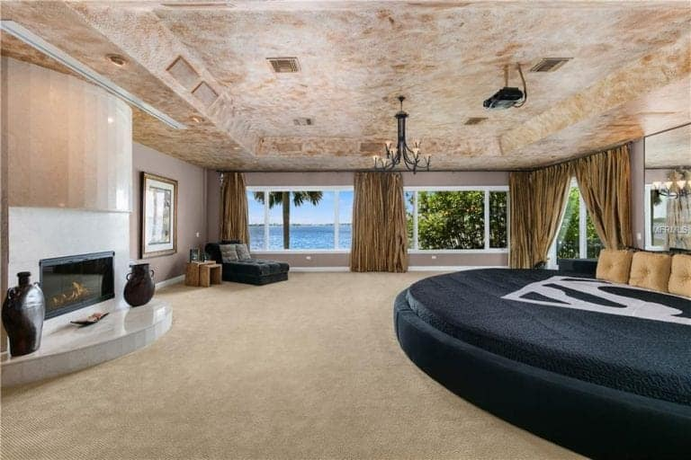 The spacious primary bedroom features a modern fireplace and a large round bed with a frameless mirror on top. It has a tray ceiling and glass paneled windows that overlook a stunning ocean view.