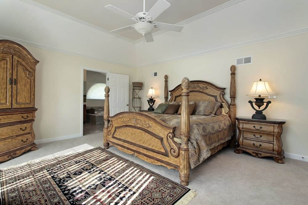 An arched wardrobe complements the four poster bed and nightstands topped with gorgeous table lamps. It has a white ceiling fan and a tasseled rug that lays on the carpet flooring.