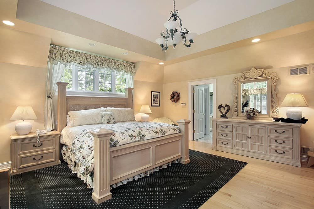 A gorgeous mirror sits on the light wood dresser in this charming bedroom with a floral skirted bed on a black dotted rug lighted by a lovely chandelier.