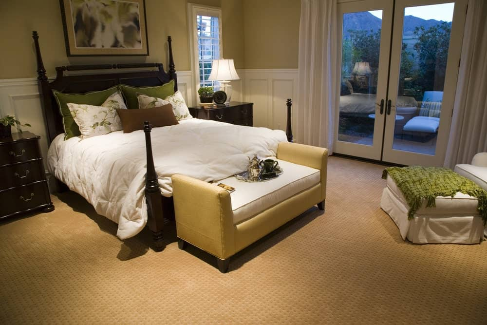 Green throw blanket and pillows add a nice accent in this beige bedroom with cozy seats and a four poster bed complementing with the dark wood nightstands.