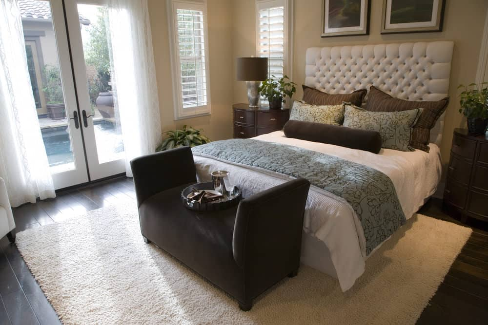 A beige area rug lays on the wide plank flooring in this primary bedroom boasting a gorgeous white bed and a French door that opens to the sparkling swimming pool.