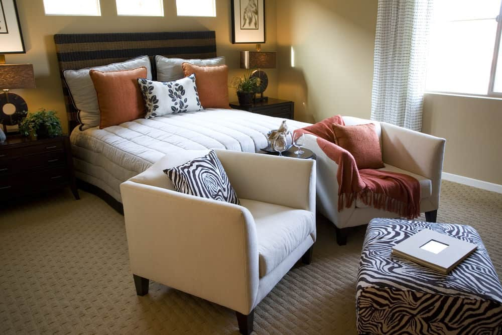 This primary bedroom is decorated with black framed artworks and round table lamps that sit on dark wood nightstands. It has a cozy bed and a seating area on its end offering beige armchairs and a zebra print ottoman.